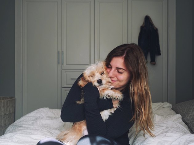 Young woman cuddling small dog in a bedroom