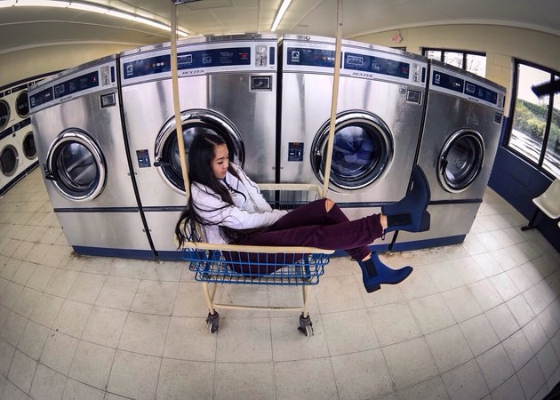 Woman sitting in rolling basket at laundromat