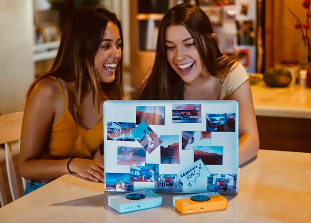 Two women smiling over laptop together