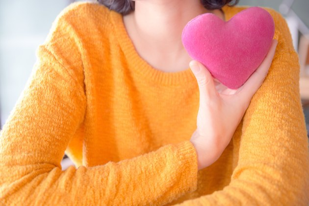 Woman in orange sweater holding pink plush heart