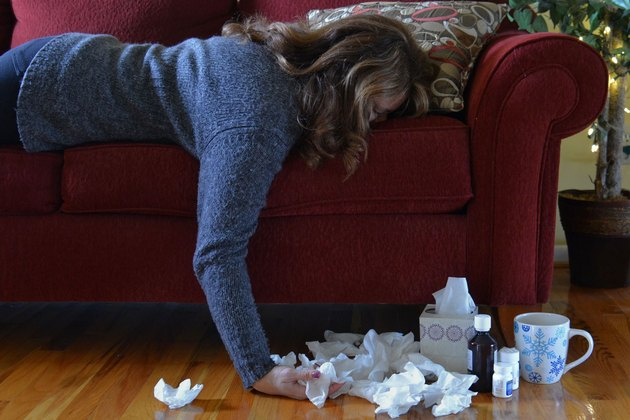 Woman lying on couch with used tissues on the floor