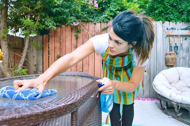 Woman cleaning an outdoor patio glass table