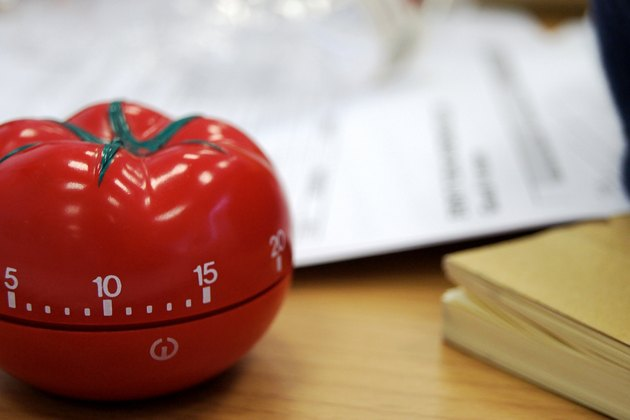 A tomato timer on a desk with papers