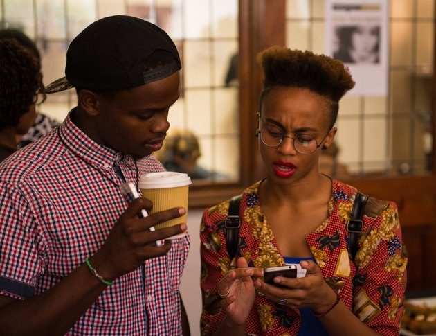 Two Black college students checking their phones