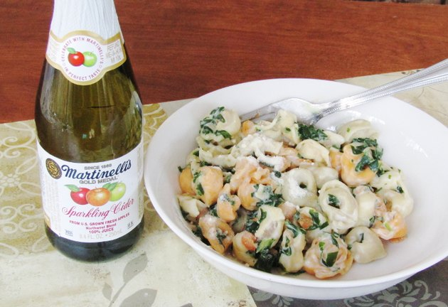finished tortellini dish with a bottle of sparkling cider