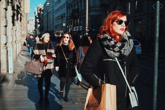 Redheaded women walking down street winter holiday shopping