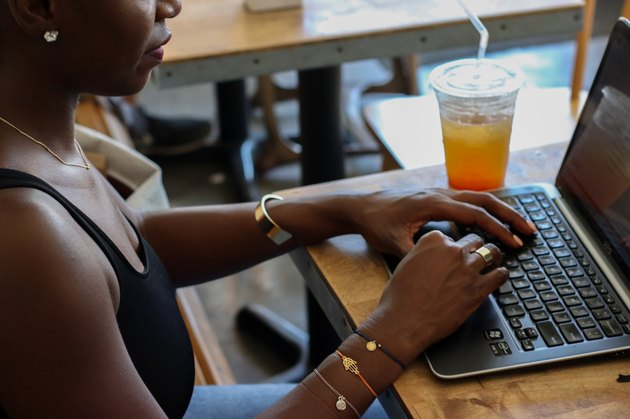 Black woman in coffee shop on laptop
