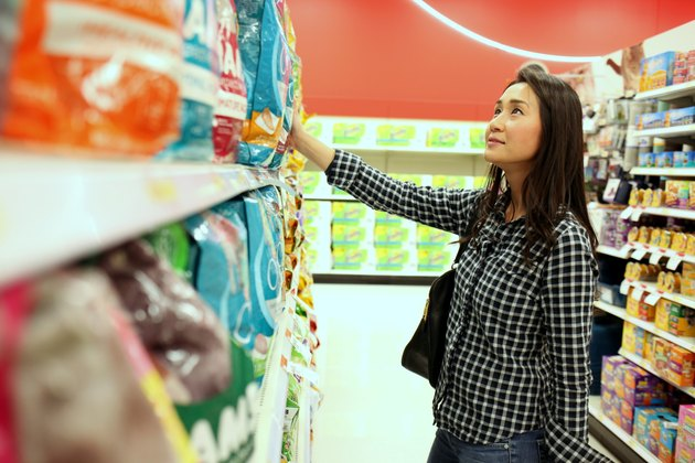 Woman grocery shopping looking at rows of chips