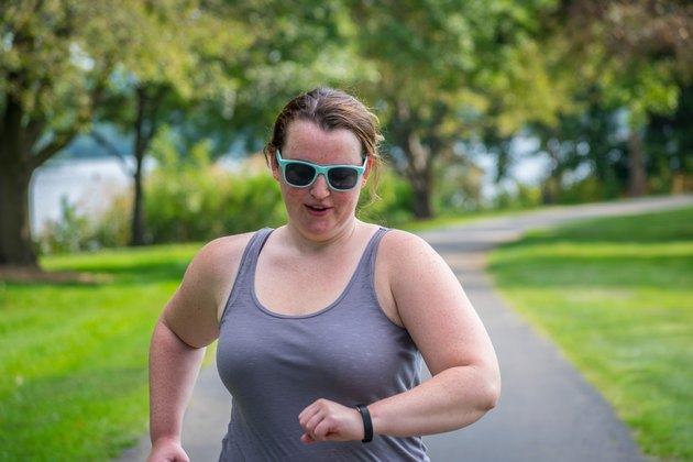 Young woman running with FitBit