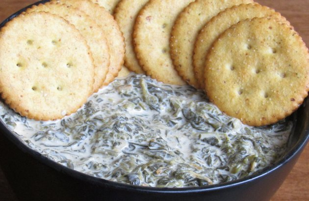 A bowl of spinach dip topped with a row of round crackers.