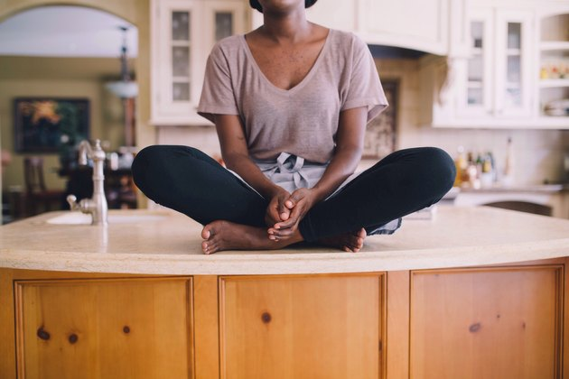 Young Black woman sitting cross-legged on kitchen counter