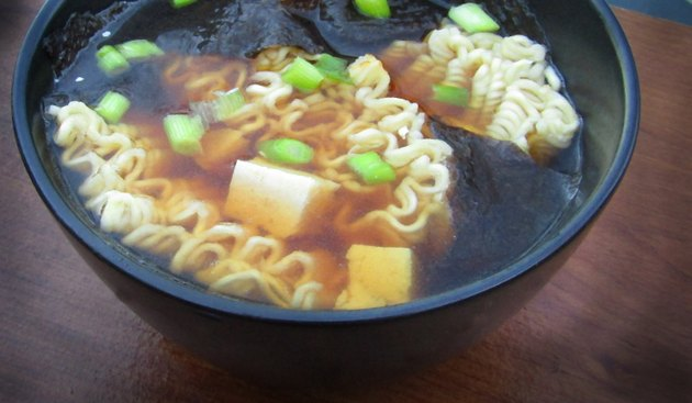 A bowl of miso ramen noodle soup with tofu, nori, and scallions.