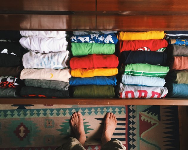 Person (feet) in front of open clothing drawer with folded shirts