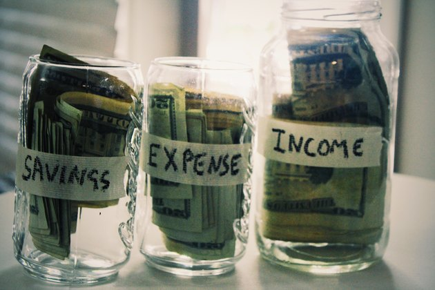 Labeled jars with American dollars inside - savings, expense, income