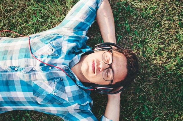 Young man lying in grass listening to headphones