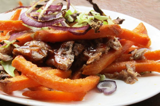 A plate of sweet potato fries topped with pulled pork, shredded cabbage, and sliced onions.