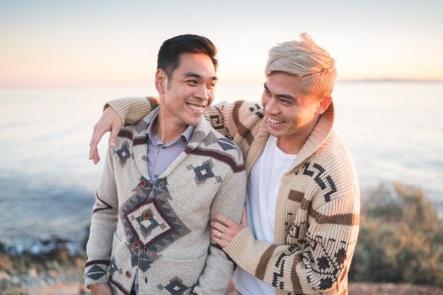 Two gay Asian men in adorably ugly sweaters being affectionate