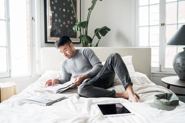 Man in comfortable clothes reading on a bed