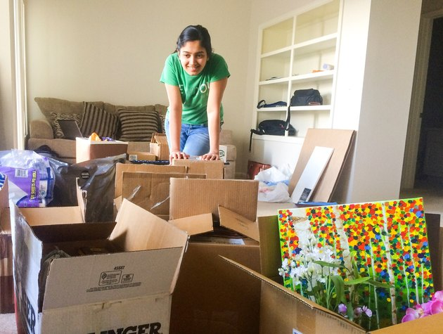 Young woman packing or unpacking boxes in apartment