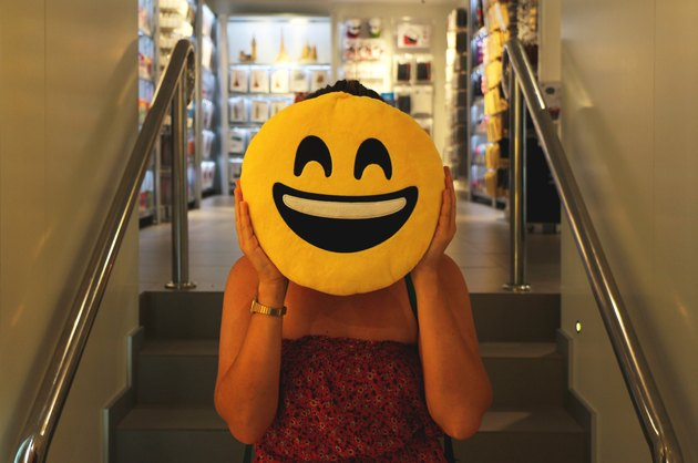 Woman holding emoji pillow over her face