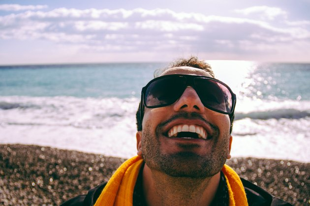 Young man in sunglasses laughing on beach