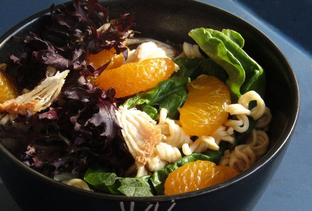 A bowl of green and purple lettuce with chicken, ramen noodles, and mandarin orange slices.