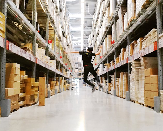 Man jumping in IKEA warehouse aisle