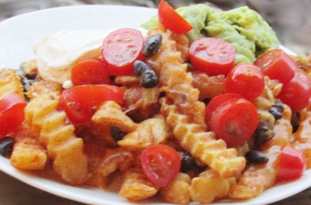A plate of french fries topped with black beans, cheese, tomatoes, sour cream, and guacamole.