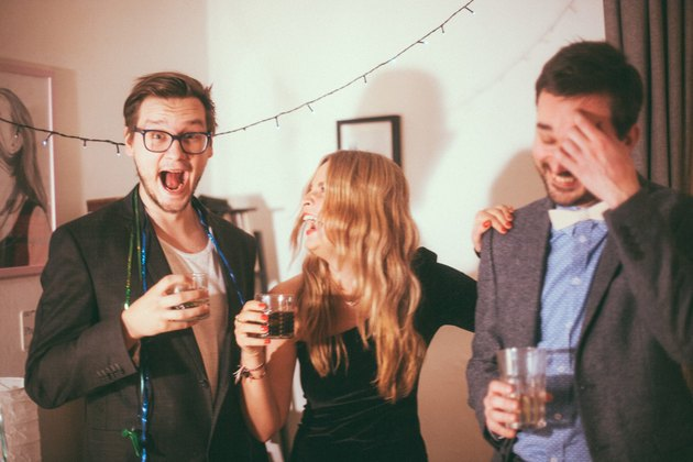 three friends laughing and drinking together at a NYE party