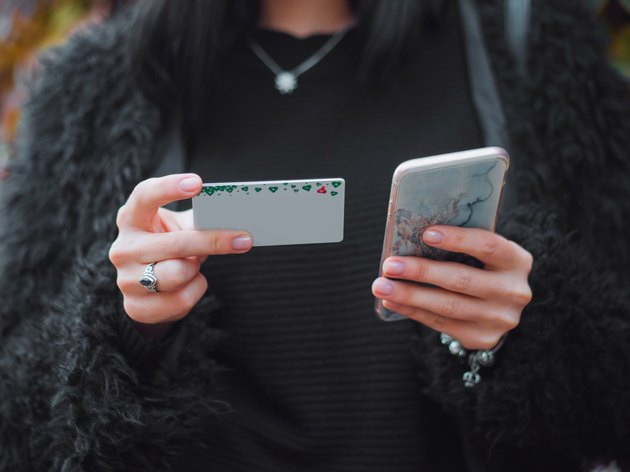 Woman holding holiday card and phone