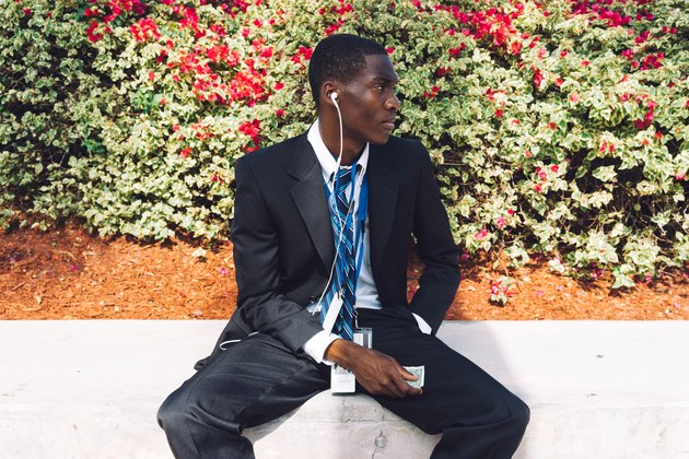 Seated young Black man in suit listening to headphones