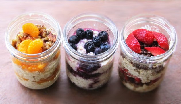 3 jars full of fruit and oatmeal, one with oranges and walnuts, one with blueberries, and one with strawberries and chocolate chips.