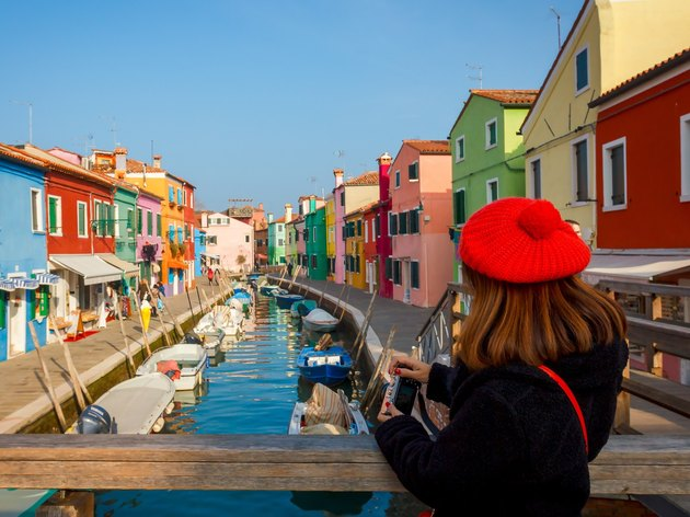 Woman holding wallet on colorful canal