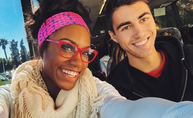 Two young diverse people taking a selfie on a bus