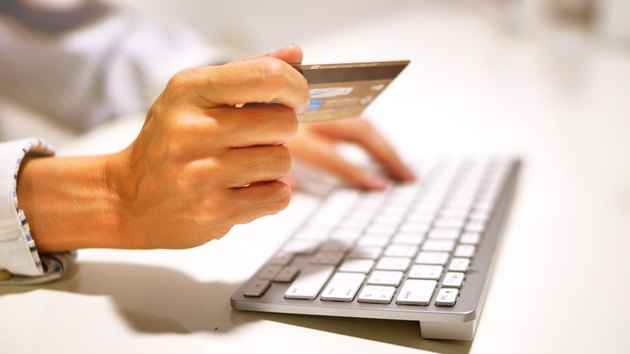 Hands hold credit card at keyboard