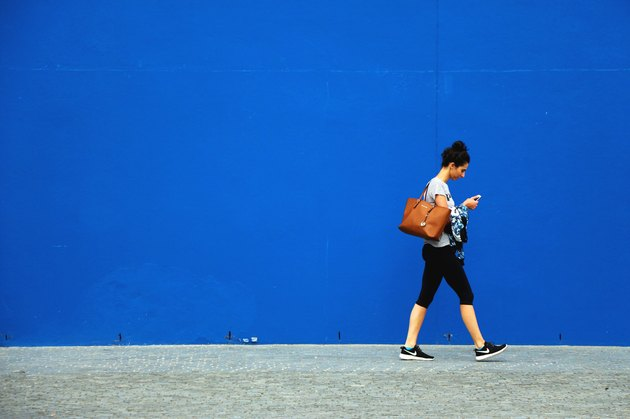 Young woman walking in front of blue wall outside