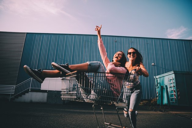 Two hipster women playing around in a shopping cart