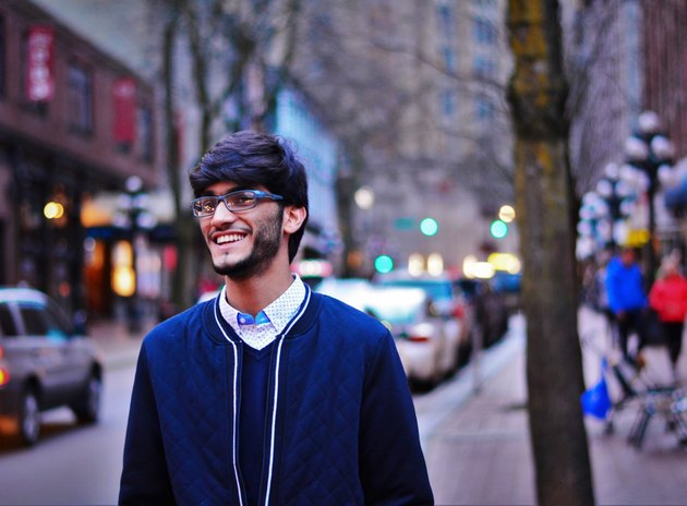 Young South Asian man walking down street smiling