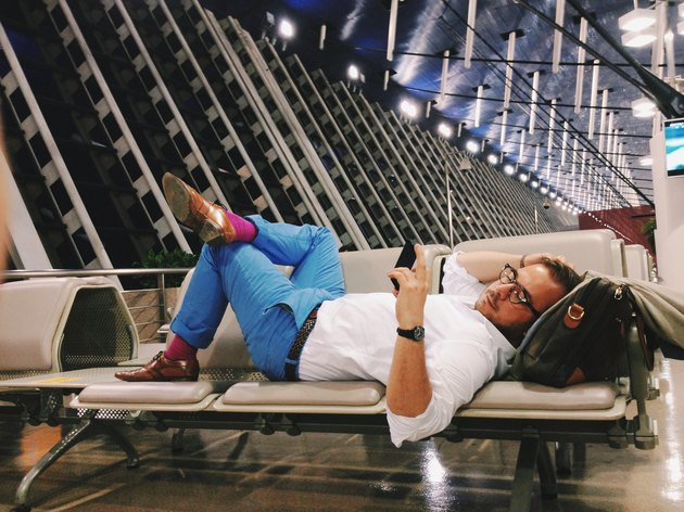 Man lying on seats at airport gate