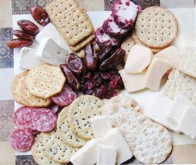 A display of sliced cheese, salami, cranberries, dates, and crackers.