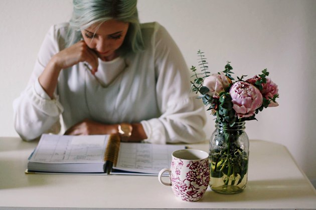 Young woman with mug and peonies reading planner