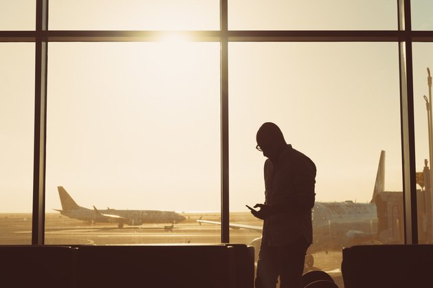 Man waiting at airport gate checking his phone