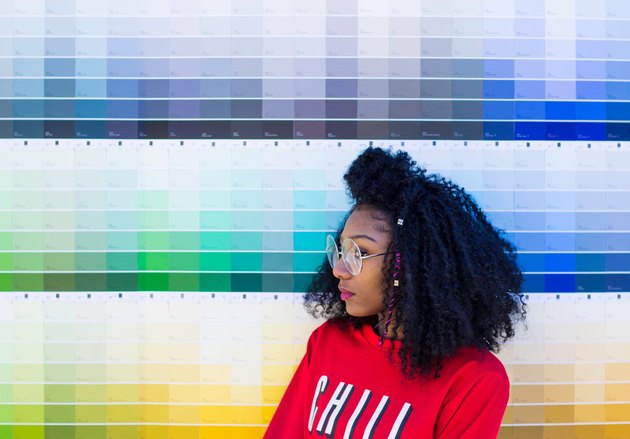 Young Black woman standing in front of paint swatches