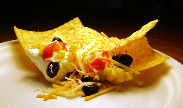 Tortilla chips dipped in sour cream, corn, black beans, hot sauce, and shredded cheese.