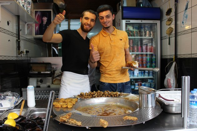 Two young men working at an ethnic restaurant