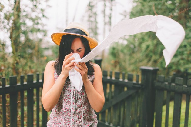 Young woman sneezing into a long floating strip of toilet paper