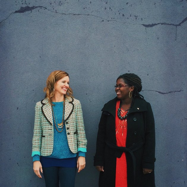 Two young professional women smiling in front of a wall