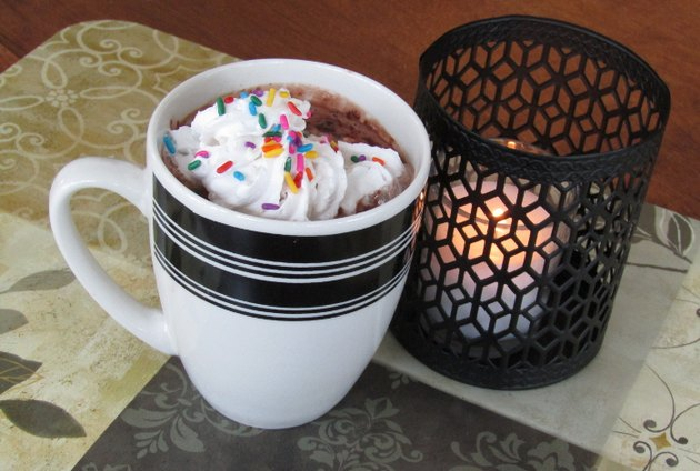 mug of hot chocolate next to a candle