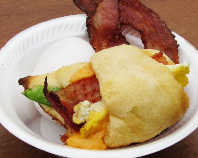 Baked crescent roll stuffed with bacon, egg, cheese and green pepper, in the background there are 2 slices of bacon and an egg.