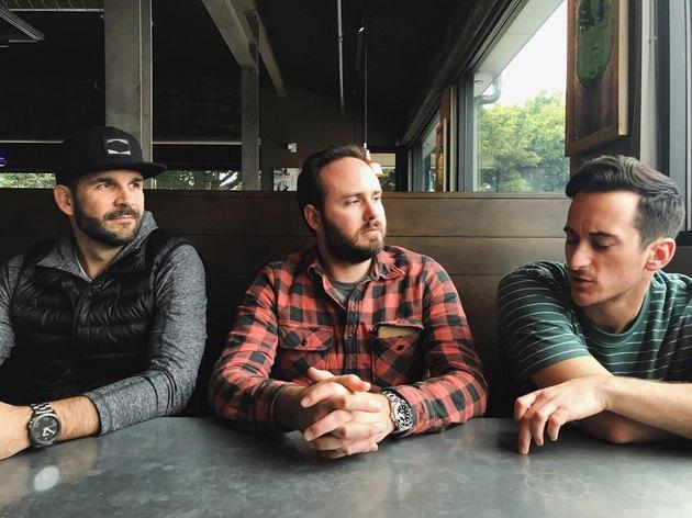 Three men conversing in a restaurant booth